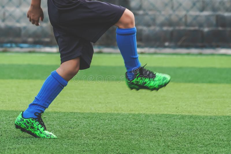 Pies del niño que practican el funcionamiento y el retroceso de la bola con el pie en campo de fútbol foto de archivo