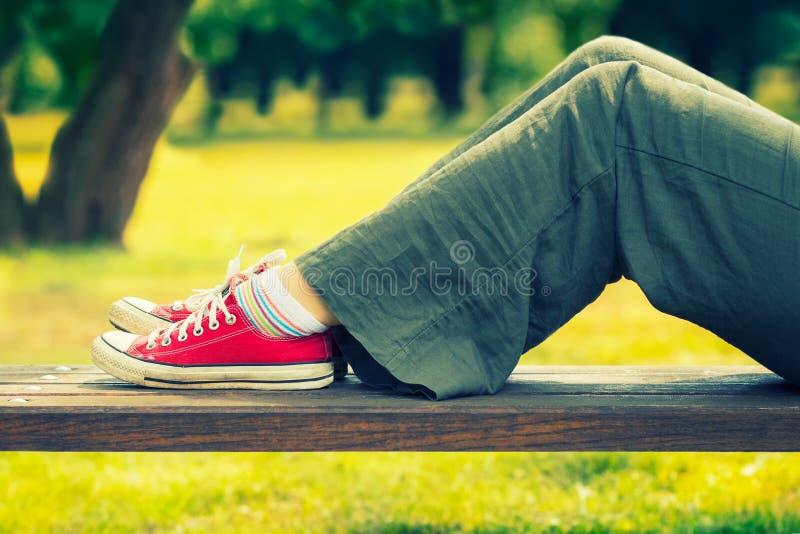 Pies del ` s de la mujer en zapatillas de deporte rojas brillantes de la lona imagenes de archivo