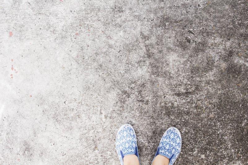 Pies del ` s de la mujer en zapatos para andar en la carretera de asfalto Foto concreta industrial de la opinión superior del pis imágenes de archivo libres de regalías