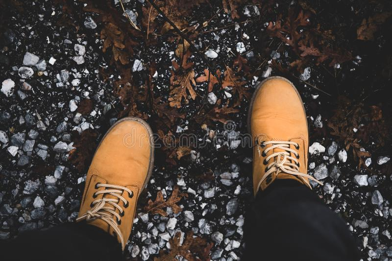 Pies del viajero en las botas amarillas que se colocan en la montaña fotografía de archivo