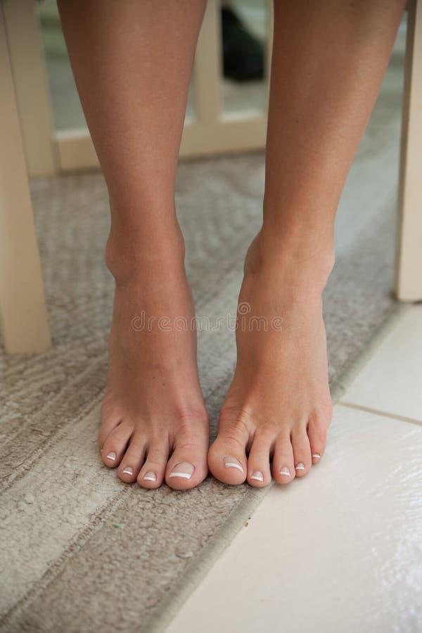 Pies descubiertos y piernas de la mujer fotos de archivo