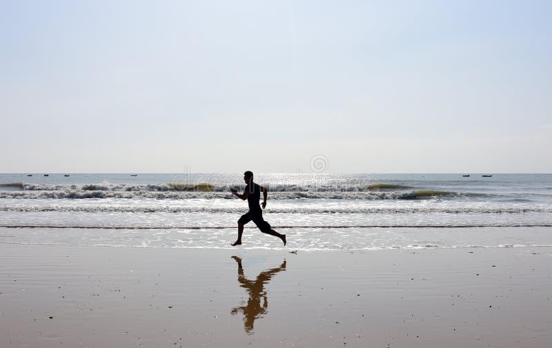 Pies desnudos de hombre que corre en la playa fotografía de archivo
