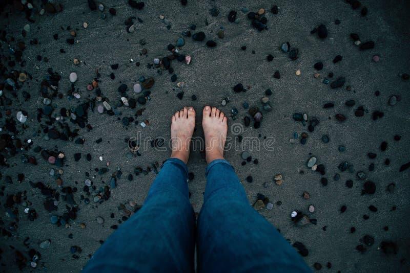 Pies desnudos de la mujer con los tejanos en la arena negra y la opinión superior de las piedras fotos de archivo libres de regalías