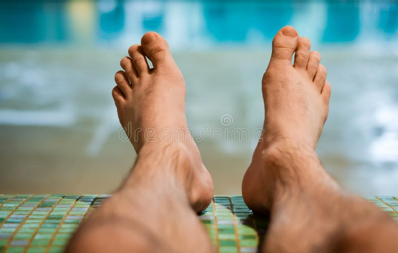 Pies desnudos del hombre que se sientan en el banco en la piscina interior imagen de archivo