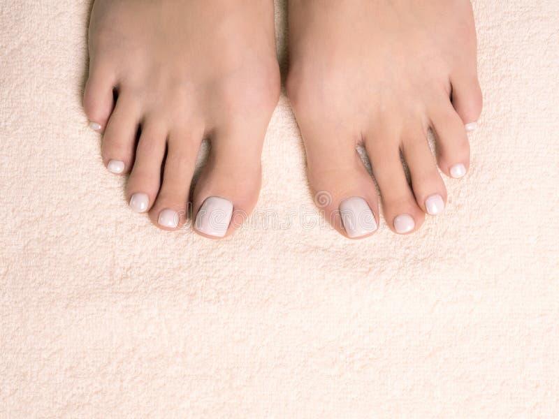 Pies desnudos femeninos, dedos del pie con la pedicura blanca en la toalla de Terry de marfil, cierre para arriba fotos de archivo libres de regalías