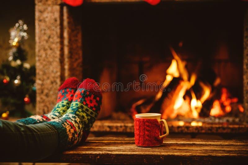 Pies en calcetines de lana por la chimenea de la Navidad La mujer se relaja imagen de archivo libre de regalías