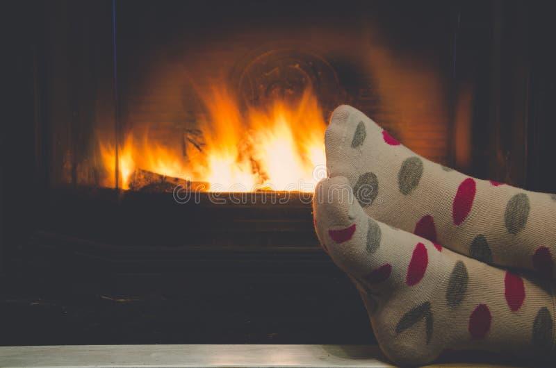 Pies en calcetines de toda la familia que se calienta por el fuego acogedor imagenes de archivo