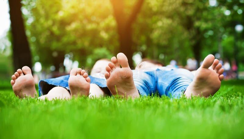 Pies en hierba. Comida campestre de la familia en parque del resorte fotografía de archivo libre de regalías
