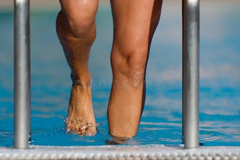 Pies en los pasos de la piscina fotografía de archivo libre de regalías