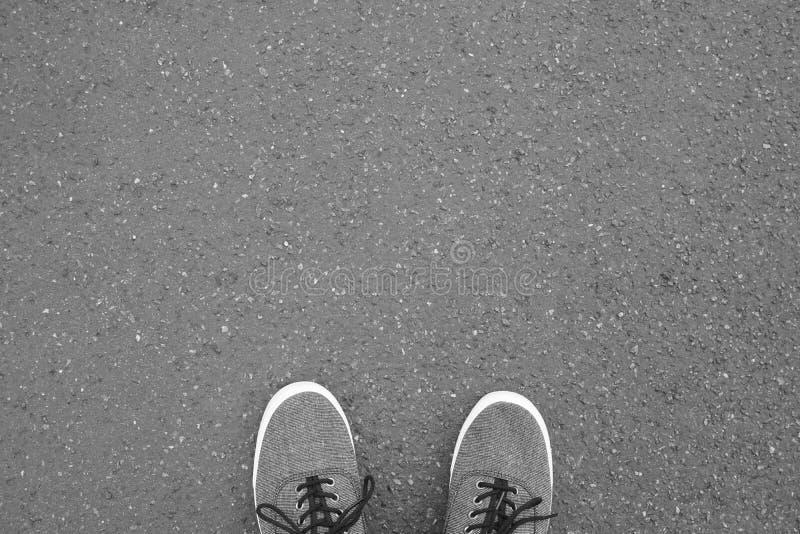 Pies en los zapatos de lona que se colocan en la calle del asfalto fotos de archivo