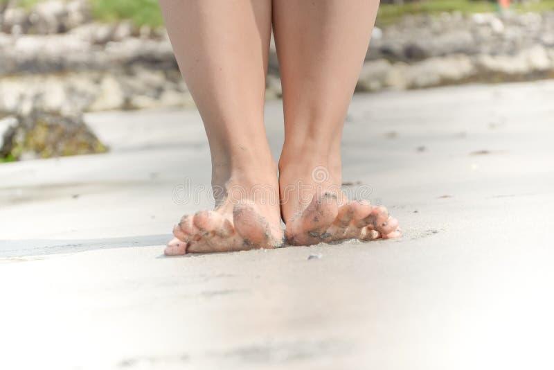 Pies en una playa - los pies desnudos de la mujer en la arena imagen de archivo libre de regalías
