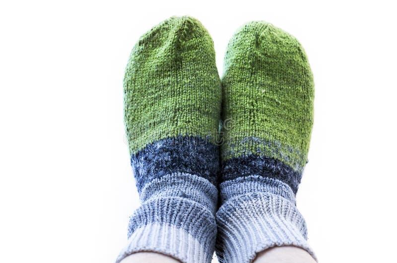 Pies en verde y Gray Handmade Knitted Woollen Socks en el fondo blanco Guardando usted mismo concepto caliente imágenes de archivo libres de regalías