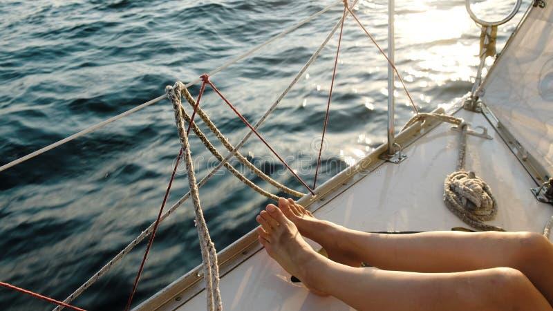 Pies femeninos de las piernas en el primer navegante del yate en el mar abierto fotos de archivo