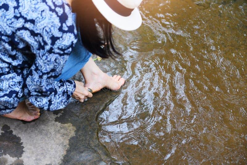 Pies femeninos del balneario que limpian con la piedra en la corriente del río de la naturaleza - mujer que hace sus pies fregar, foto de archivo
