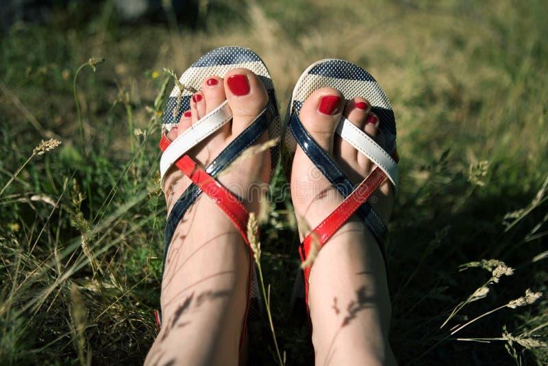 Pies femeninos en sandalias foto de archivo libre de regalías