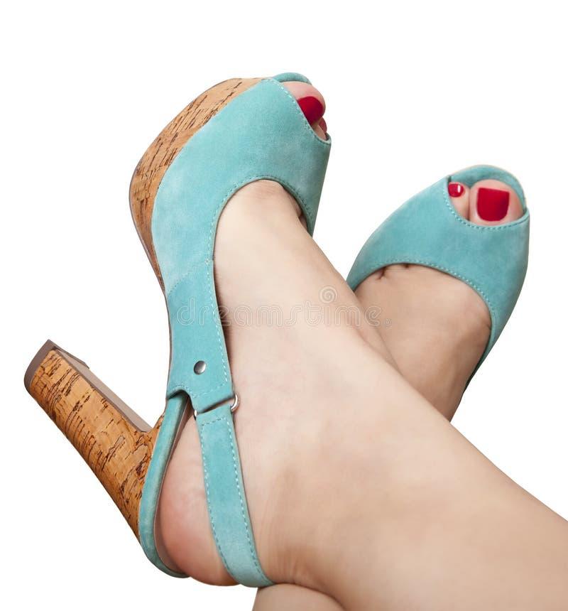 Pies femeninos en sandalias en un talón imagen de archivo