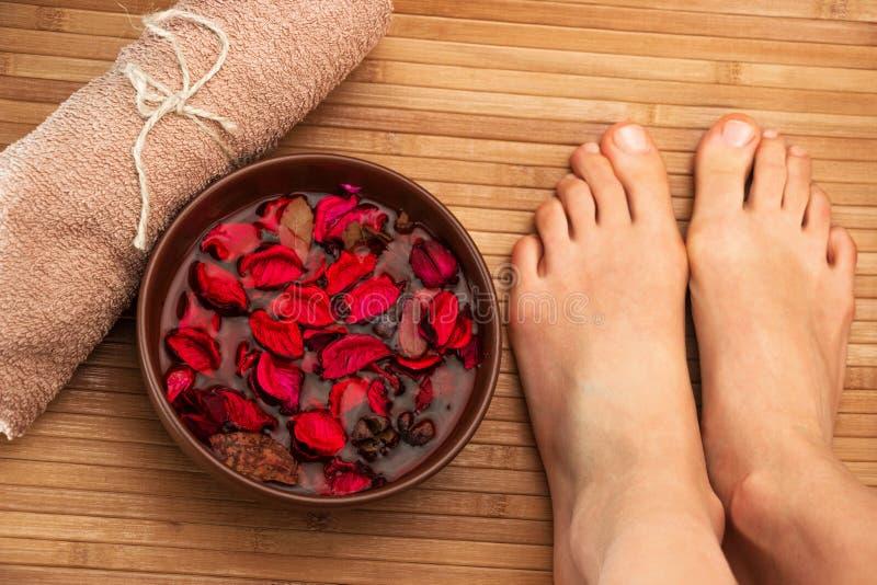 Pies femeninos hermosos, salón del balneario, procedimiento de la pedicura con los pétalos de la flor de la rosa del rojo fotos de archivo
