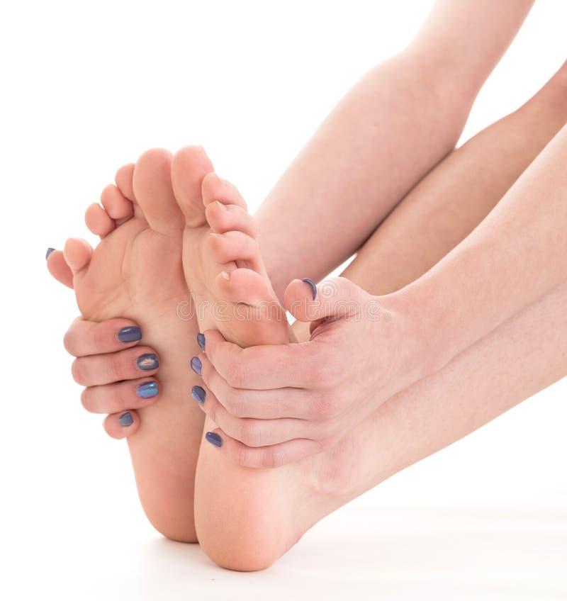 Pies femeninos sensuales sobre el fondo blanco Mujer que da masajes a las piernas fotografía de archivo