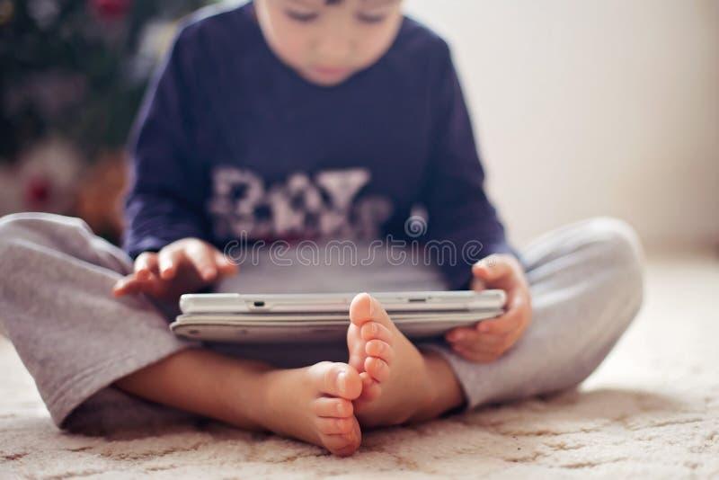 Pies lindos de los niños pequeños, muchacho que juega en la tableta imagenes de archivo
