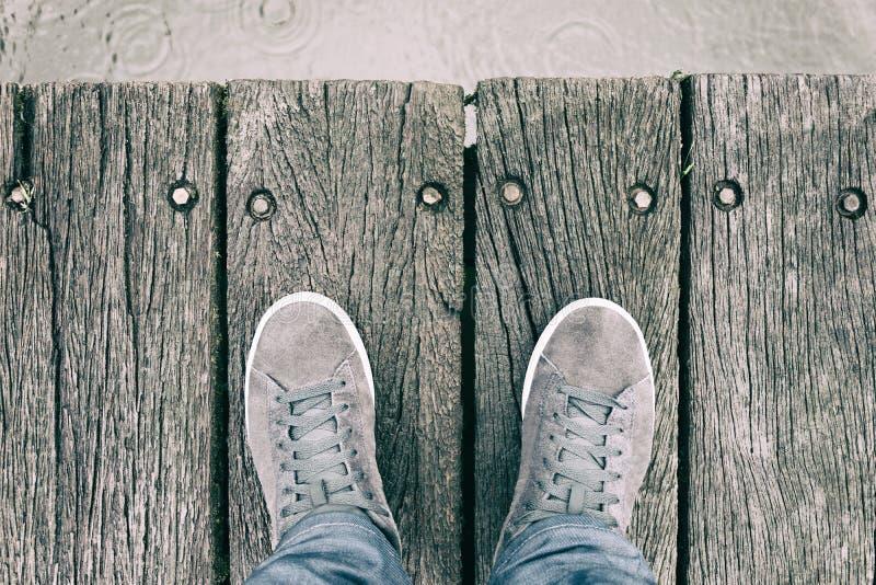 Pies masculinos con los zapatos que se colocan en el frente de madera de Pier In del mar fotografía de archivo libre de regalías