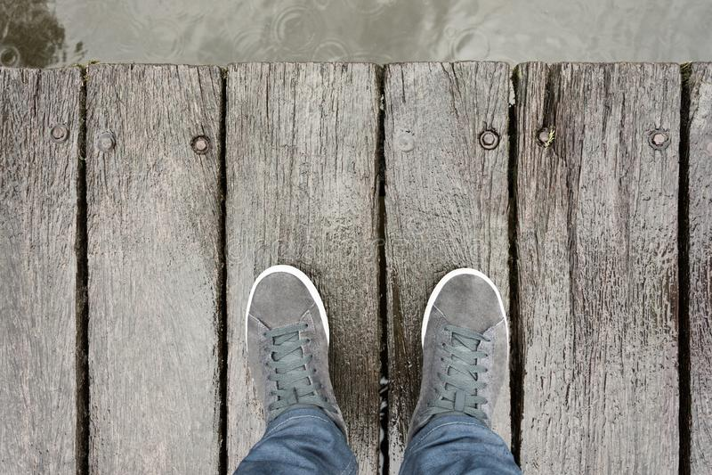Pies masculinos con los zapatos que se colocan en el frente de madera de Pier In del mar foto de archivo