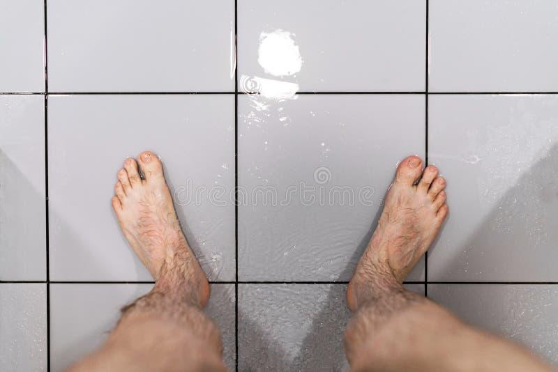 Pies masculinos en ducha Concepto de problema con potencia Salud del ` s del hombre imágenes de archivo libres de regalías