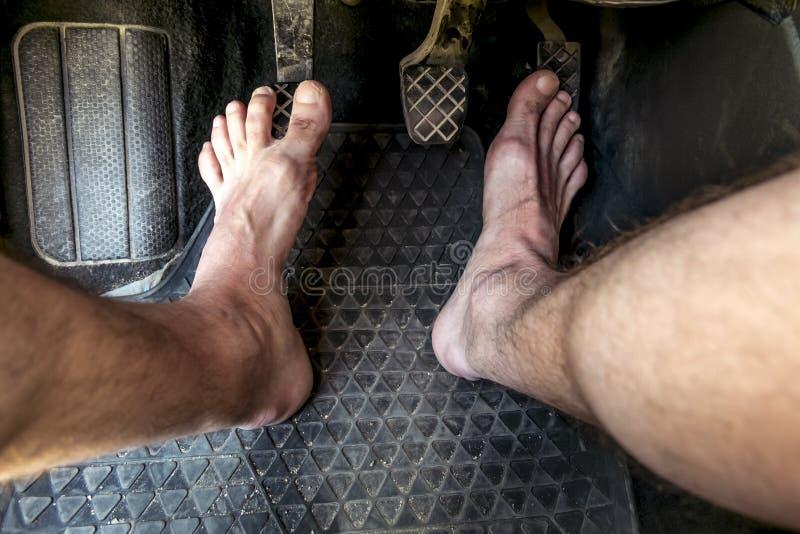 Pies masculinos en los pedales del freno y de acelerador en un coche fotografía de archivo libre de regalías