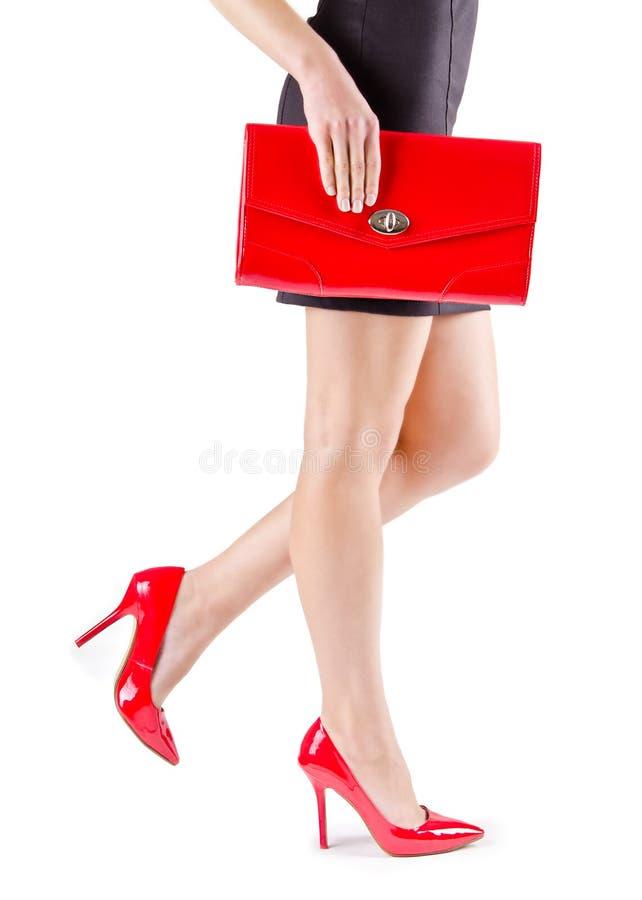 Pies mujeriles hermosos delgados en zapatos rojos y mini bolso foto de archivo
