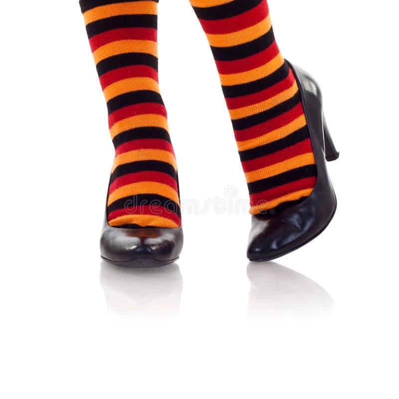 Pies que desgastan calcetines coloreados en altos talones foto de archivo
