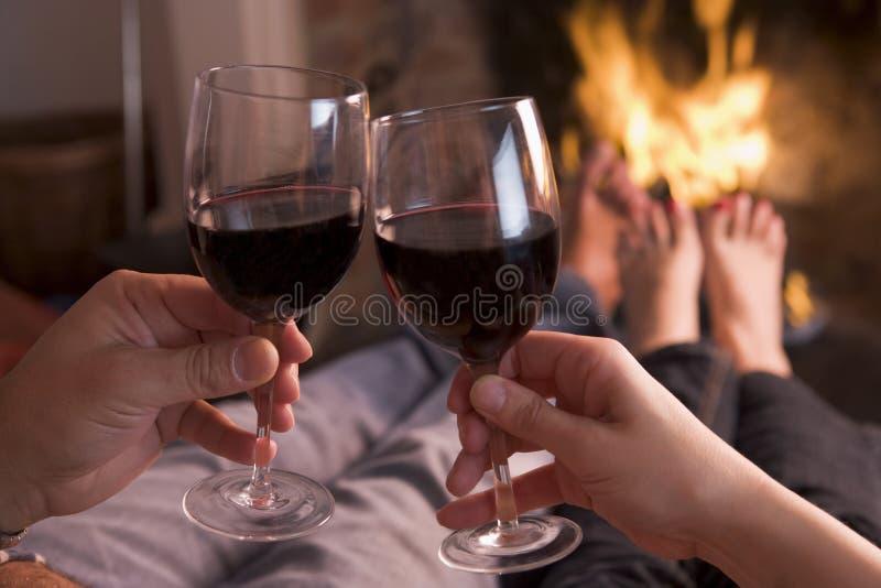 Pies que se calientan en la chimenea con las manos que sostienen el vino foto de archivo libre de regalías
