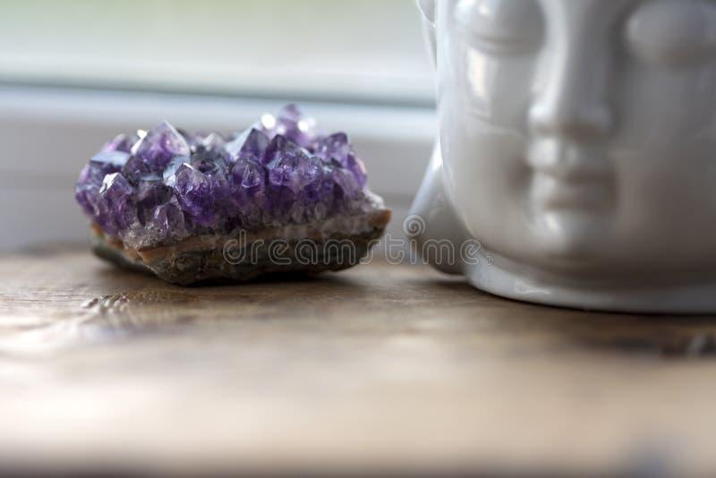 Pietra ametista porpora e gemmy con la testa bianca di Buddha sui precedenti di davanzale Cristalli ruvidi di ametist sulla casa fotografie stock