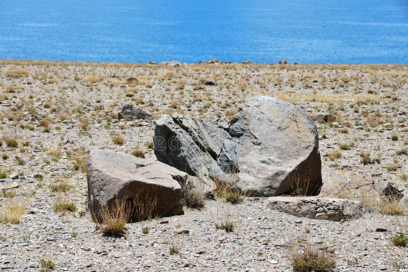 Pietra, come un cuore rotto o un viso umano nel profilo, sulla riva del lago tibetano sacro Tere Tashi Namtso fotografie stock