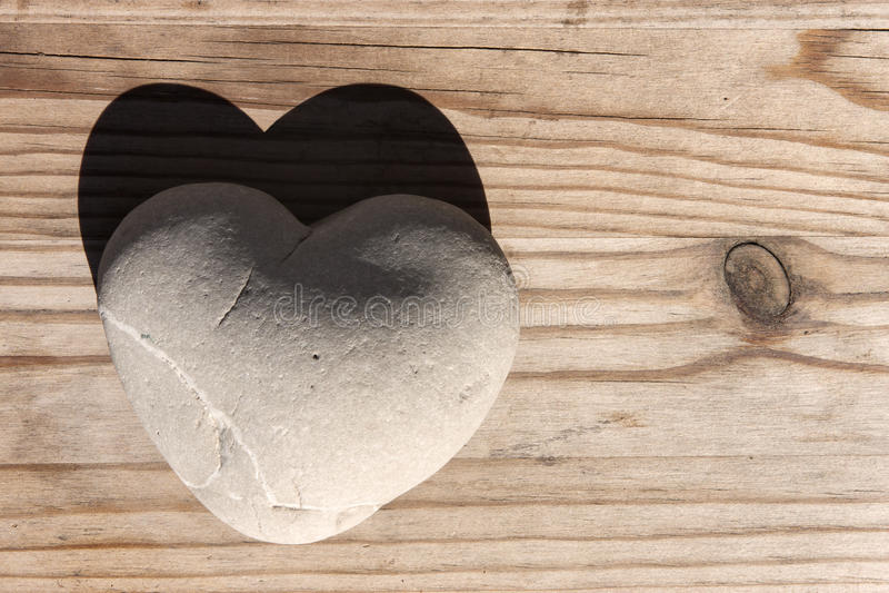 Pietra del cuore con ombra sulla tavola di legno fotografia stock