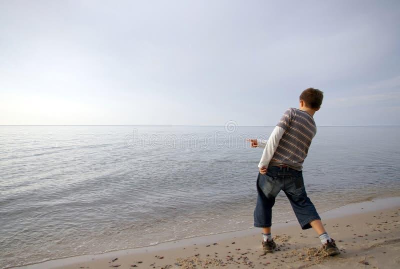 Pietra di lancio del ragazzo in acqua fotografia stock libera da diritti