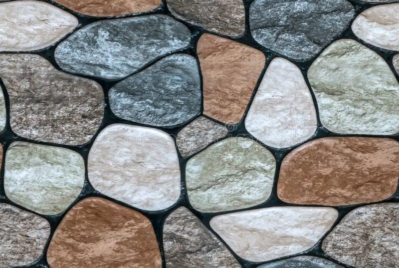 pietra multicolore con il fondo arrotondato della parete dei fronti fotografia stock