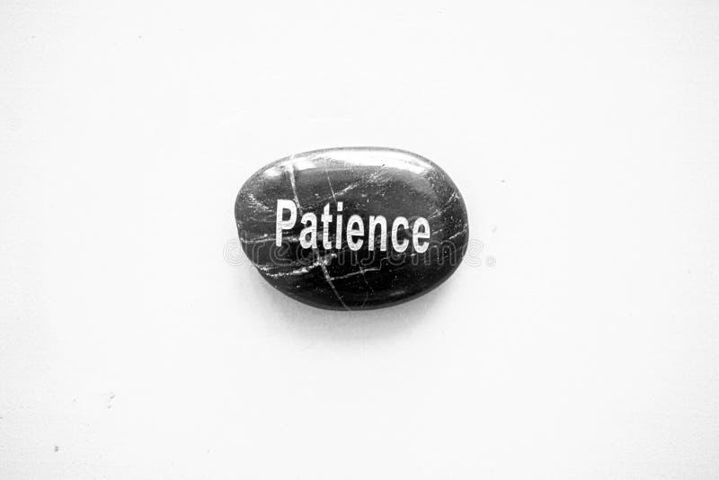 Pietra nera con pazienza di parola in bianco e nero immagini stock