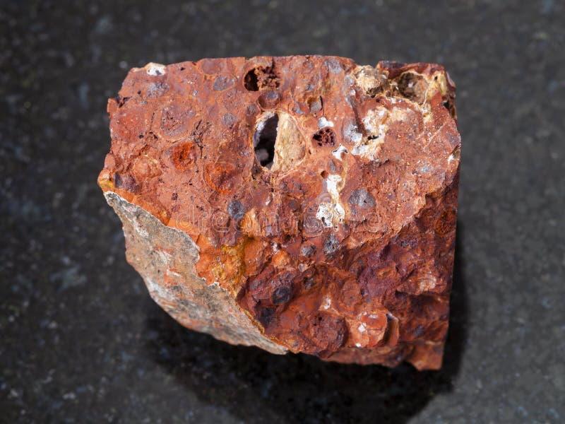 pietra rossa cruda della bauxite su fondo scuro fotografie stock