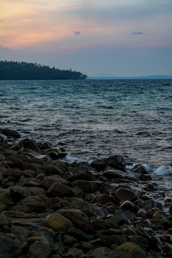 Pietra scura nera sulla spiaggia nel mare con piccole lumache tutte quell'area È tempo del twiligt in asiatico, Tailandia fotografia stock libera da diritti