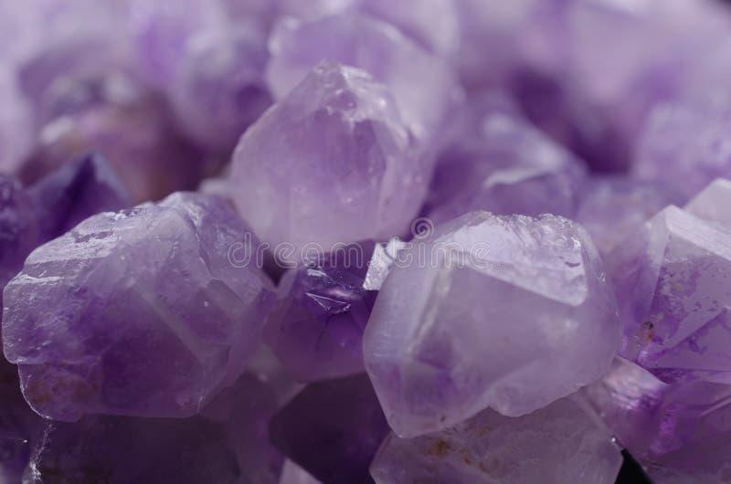 Pietre ametiste minerali multiple su un primo piano bianco del fondo fotografia stock