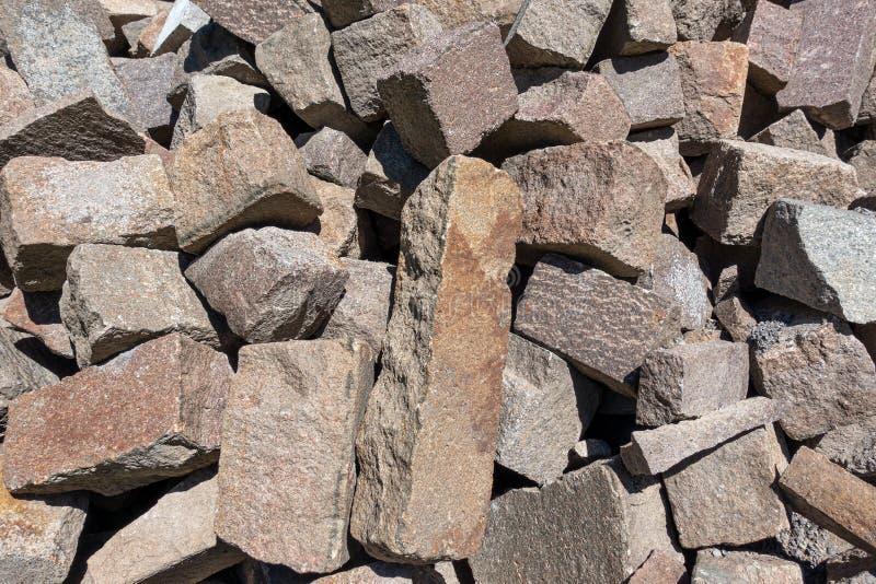 Pietre da pavimentazione in granito ruvide e rosse in un mucchio immagini stock