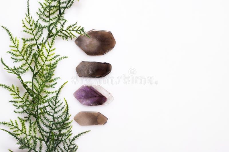 Pietre dei minerali rimosse su un fondo bianco sulla cima con erba verde immagini stock