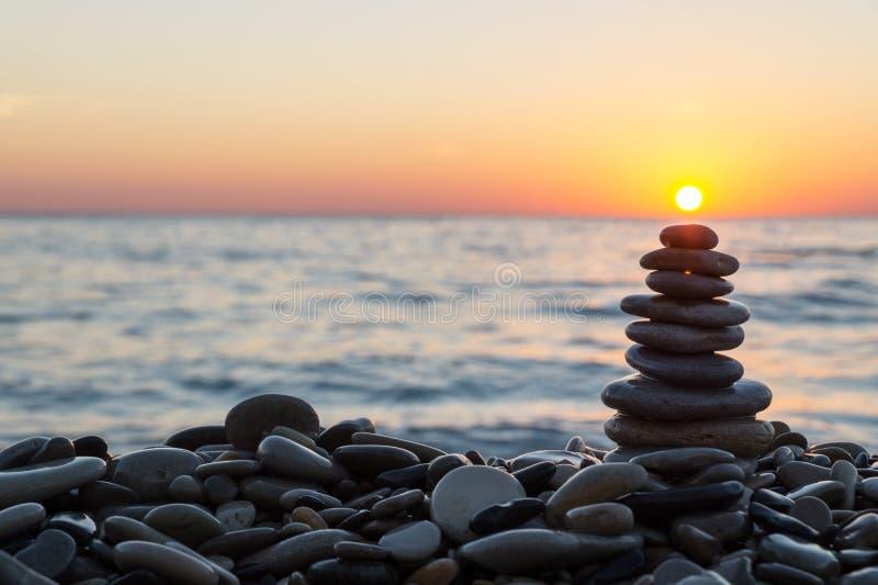Pietre del cairn con il sole sulla spiaggia sul tramonto fotografia stock libera da diritti