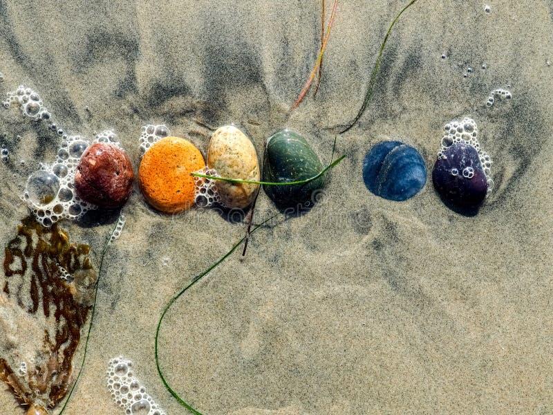 Pietre dell'arcobaleno sulla spiaggia fotografia stock
