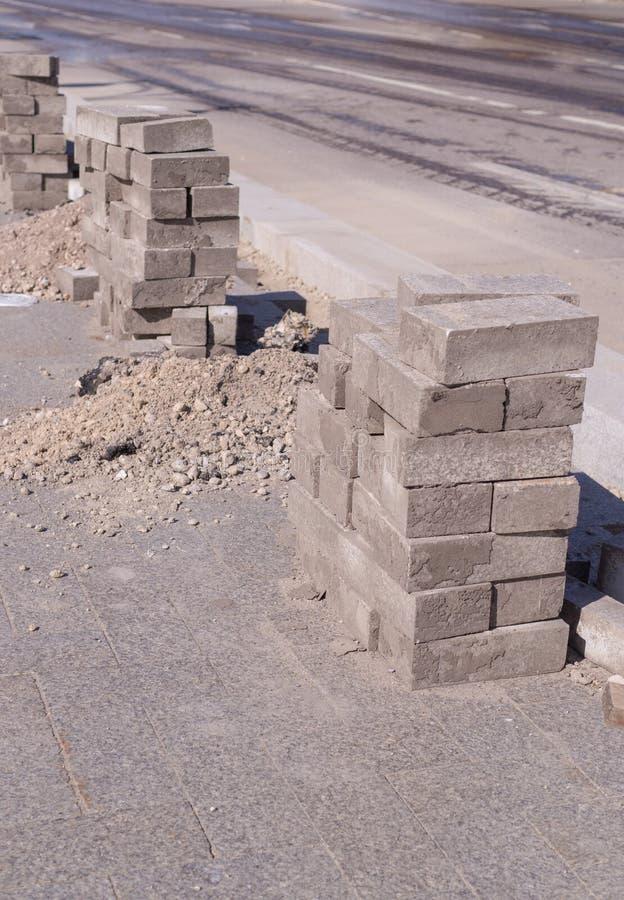 Pietre della pavimentazione impilate vicino alla strada costruzione, industriale fotografie stock libere da diritti