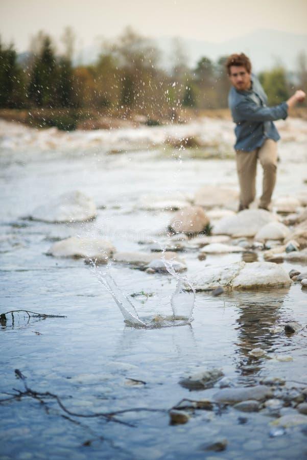 Pietre di lancio dell'uomo nel fiume immagine stock libera da diritti