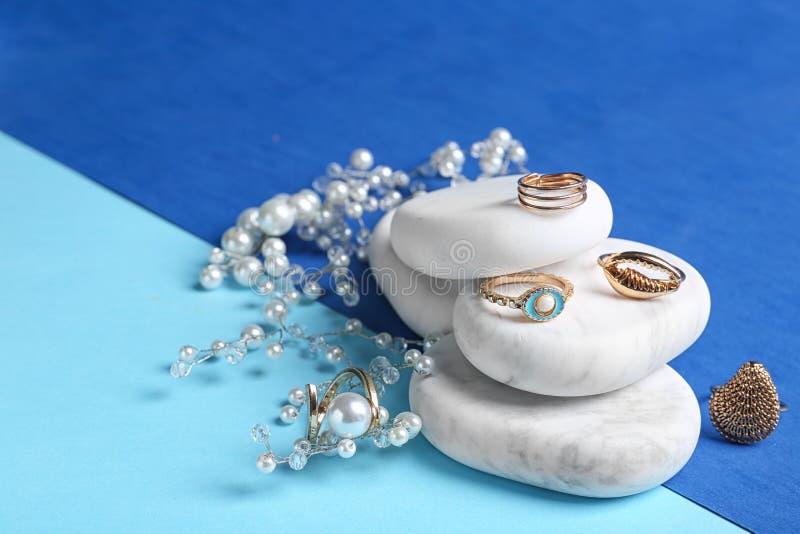 Pietre di marmo bianche con gioielli eleganti sul fondo di colore fotografie stock libere da diritti