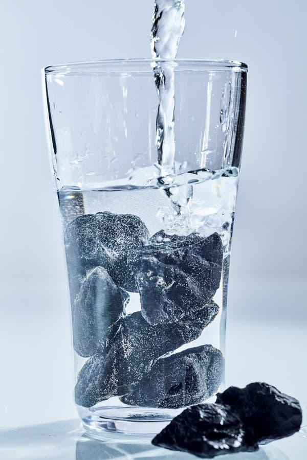 Pietre di Shungite che sono usando per purificare acqua fotografia stock libera da diritti