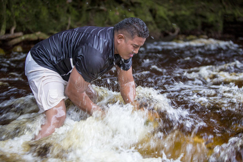 Pietre di sollevamento dell'uomo forte dal fiume, Venezuela immagine stock
