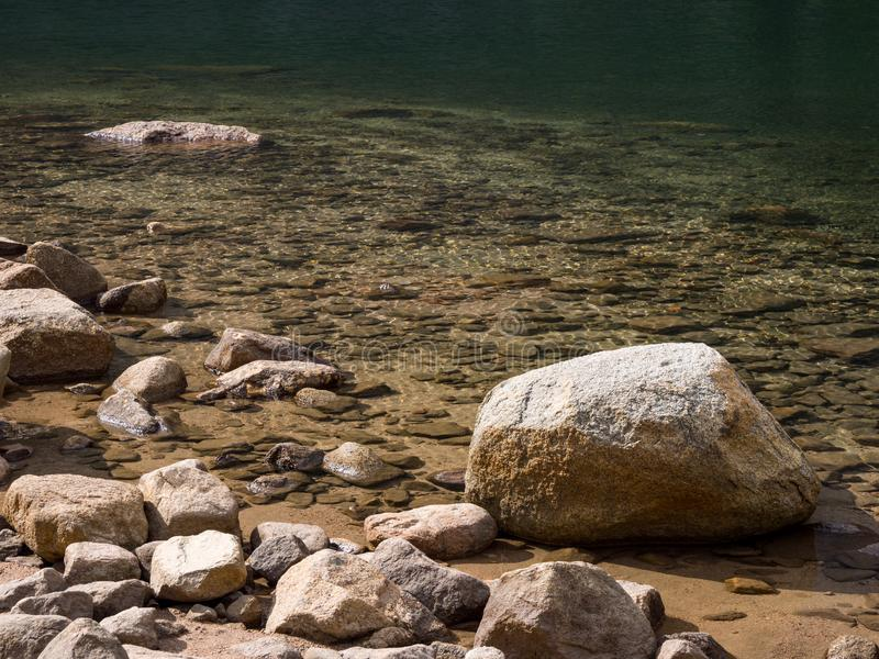Pietre e rocce lungo la riva di chiare acque immagini stock