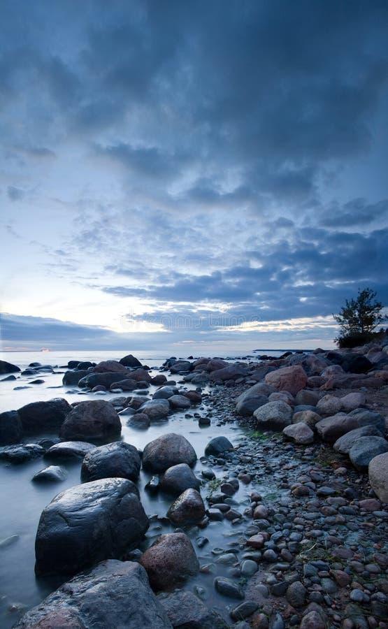 Pietre nel mare dopo il tramonto fotografia stock libera da diritti